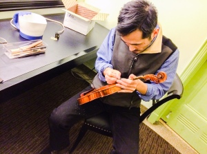 Feng Jiang repairs Mark Fewer's violin backstage at Rackham Auditorium Friday -photo credit Mark Jacobson evening.