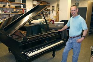 Grijalva poses with the unrestored Gershwin piano shortly after its arrival. Courtesy photo